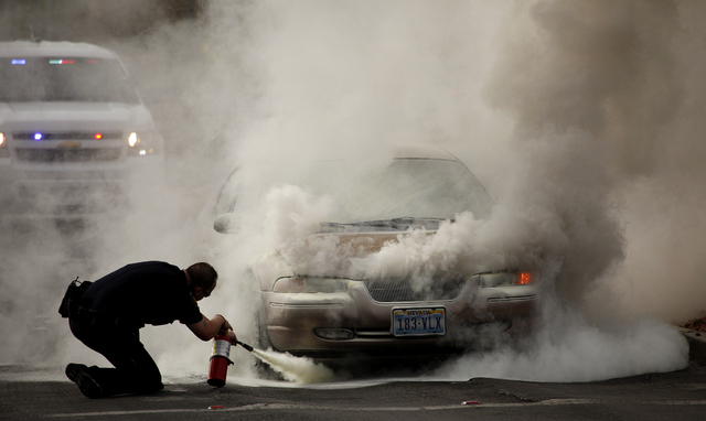 College of Southern Nevada Police Officer Michael McCleve tries to extinguish a car that caught fire at a traffic light in front of the school on Charleston Boulevard on Wednesday.  (Justin Yurkan ...