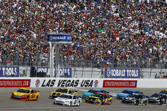 Joey Logano, in the 22 Shell Pennzoil car, leads the pack of cars across the start line at beginning of the Kobalt 400 Sprint NASCAR race at the Las Vegas Motor Speedway on Sunday, March 9, 2014.  ...