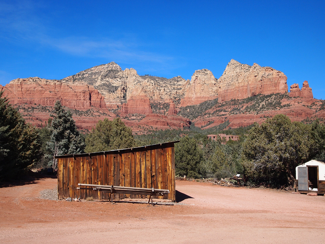 Colorful rock formations serve as a backdrop for the tractor shed at the Sedona Heritage Museum. The shed was built in 1929 by Walter Jordan to house tractors and other farm equipment for use in t ...