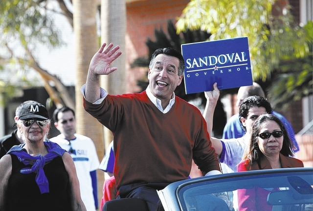 Nevada Governor Brian Sandoval waves to the crowd during the Chinese New Year parade on 4th Street in Las Vegas on Sunday, February 9, 2014. The parade is in its second year of existence and had a ...