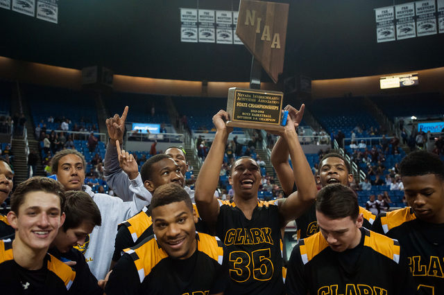 Clark players celebrate with the Division I-A state championship trophy after beating Elko 43-25 for the title. (Kevin Clifford/Las Vegas Review-Journal)