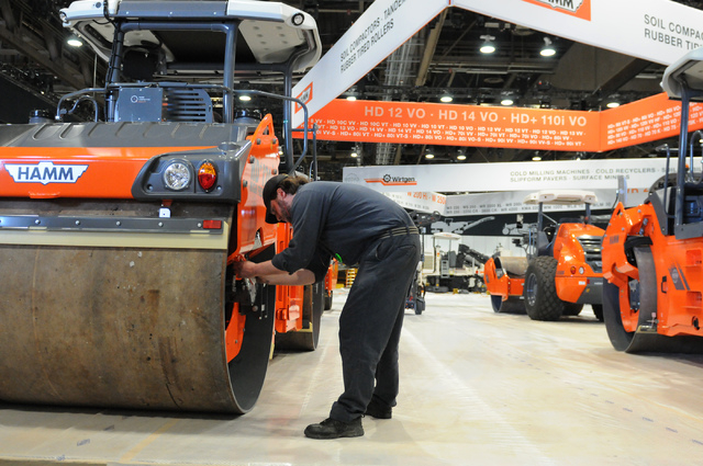 Tyler Barton, service technician at Wirtgen America, cleans construction equipment on display for the upcoming CONEXPO-CON/AGG construction show at the Las Vegas Convention Center Las Vegas Thursd ...