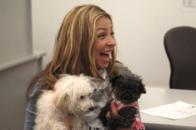 Trina Pascucci holds Aideen, left, a poodle mix that was rescued from the Prince and Princess pet store fire in January, and Maddie, a dog she has owned for years, shortly before adopting Aideen a ...
