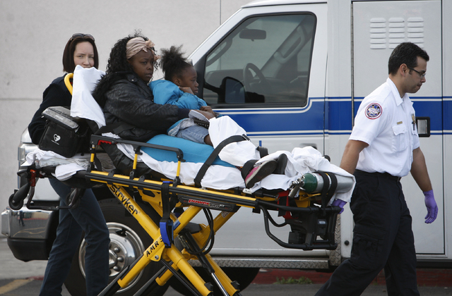 EMTs bring people to an ambulance at a Food 4 Less in Las Vegas Saturday, March 1, 2014. Nine people were hospitalized when a pickup truck plowed through the grocery store. (John Locher/Las Vegas  ...