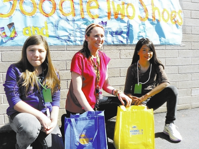 Courtesy photo  Gragson Elementary art teacher Diann Meynor, center, is shown with students Danna Palacious-Beristain, left, and Ashley Felix, who were given new shoes and socks by Goodie Two Shoe ...