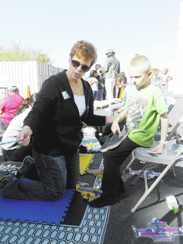 KLAS-TV Channel 8 President and General Manager Emily Neilson helps a Gragson Elementary student try on a new pair of shoes during the Goodie Two Shoes event March 14.
