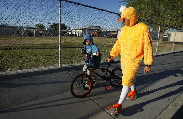 "Metro Officer Aden Ocampogomez, dressed up as a duck, helps Jonathan Becerra arrive safely at Halle Hewetson Elementary School as part of ""Walking Wednesday."" The Las Vegas Metropolitan Police Dep ..."