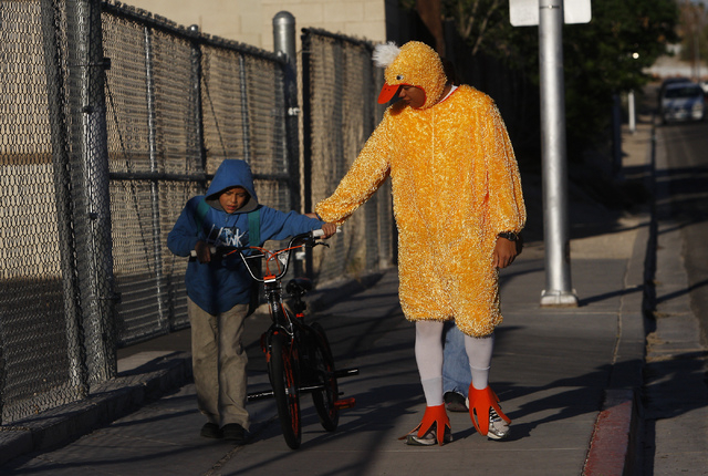 """As part of  project """"Walking Wednesday,"""" Metro Officer Aden Ocampogomez, dressed up as a duck, helps Jonathan Becerra arrive safely at Halle Hewetson Elementary School on Wednesday. The Las Vegas  ..."""