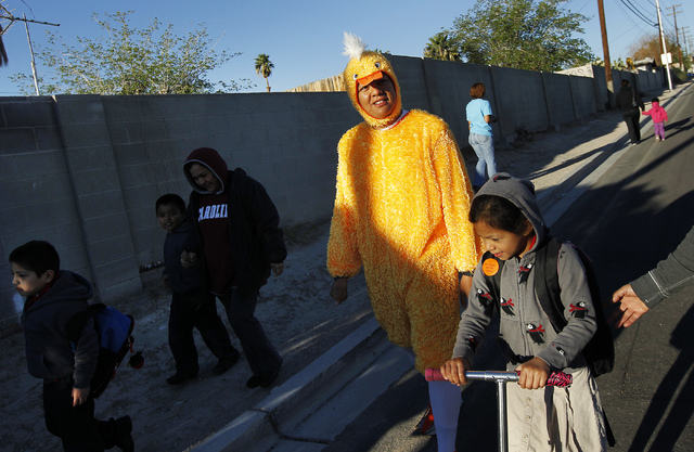 """Metro Officer Aden Ocampogomez, dressed up as a duck, helps students and their parents arrive safely at Halle Hewetson Elementary School as part of """"Walking Wednesday."""" The Las Vegas Metropolitan  ..."""