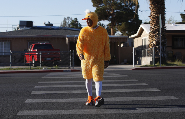 """Metro Officer Aden Ocampogomez, dressed up as a duck, watches traffic stop as he crosses Bonanza Road heading toward Halle Hewetson Elementary School as part of """"Walking Wednesday."""" The Las Vegas  ..."""