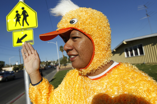 Metro Officer Aden Ocampogomez, dressed up as a duck, waves at passing traffic at the intersection of Bonanza Road and 20th Street near Halle Hewetson Elementary School. The Las Vegas Metropolitan ...