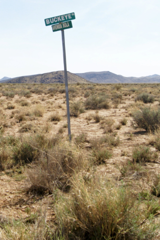 A street sign adjacent to Jim Rhodes' farm about 20 miles north of Kingman, Ariz. Friday, March 28, 2014. The builder has left his hammer in Las Vegas and taken up farming on portions of his holdi ...