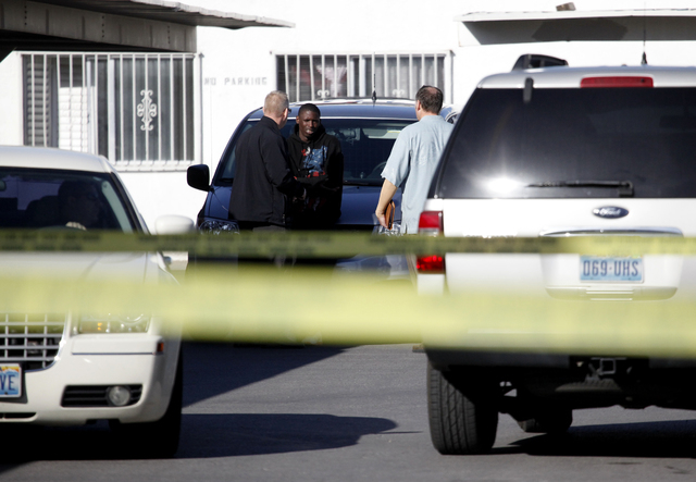 Las Vegas Metropolitan Police Department detectives speak with someone at the Desert Garden Condominium complex on West Bonanza Road near Martin Luther King Blvd. after someone was shot in the fac ...