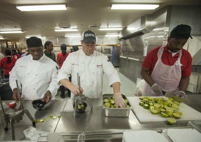 Levy Restaurants kitchen staff Eddis Spellman, left, Wayne Norris and Neal Sapreein slice limes in the Levy Restaurants kitchen at  Las Vegas  Motor Speedway on Thursday. The restaurant is making  ...