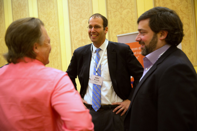 Mike Rozman, co-president and chief strategy officer of BoeFly, center, networks with Rodney Eckerman, left, co-CEO and president of PizzaRev, and Jim Ellis, right, with Capital Spring LLC, during ...