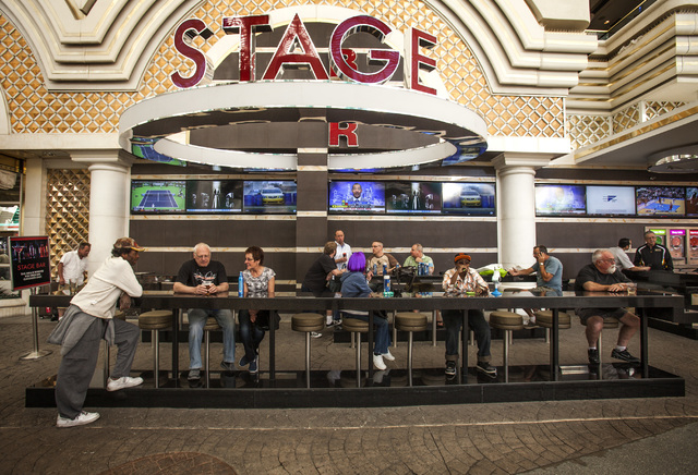 Patrons gathers at the Stage Bar outside the Golden Nugget  hotel/casino on Friday, March 14, 2014. The exterior casino bars under Fremont Street Experience canopy that's pitting small casino owne ...