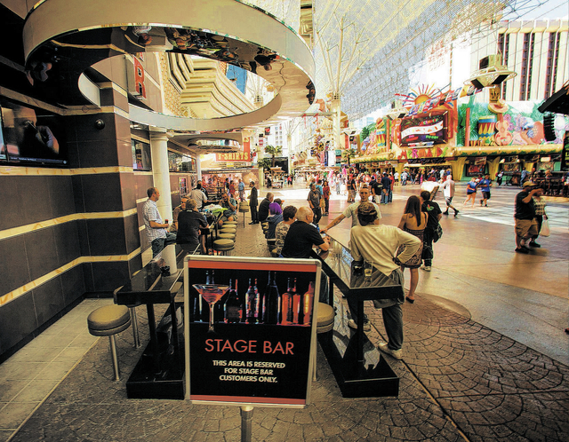 Patrons gathers at the Stage Bar outside the Golden Nugget  hotel/casino  on Friday, March 14, 2014. The exterior casino bars under Fremont Street Experience canopy that's pitting small casino own ...