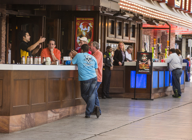 Patrons stand at the Golden Gate hotel/casino outdoor bar on Friday, March 14, 2014. The exterior casino bars under Fremont Street Experience canopy that's pitting small casino owner Steve Burnsti ...