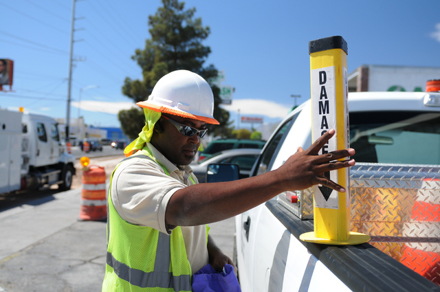 """""""Robbie"""", who did not want to give his full name, grabs a sign from his truck at the site of a gas leak where crews with Southwest Gas and ELM Locating and Utility Services worked to rep ..."""