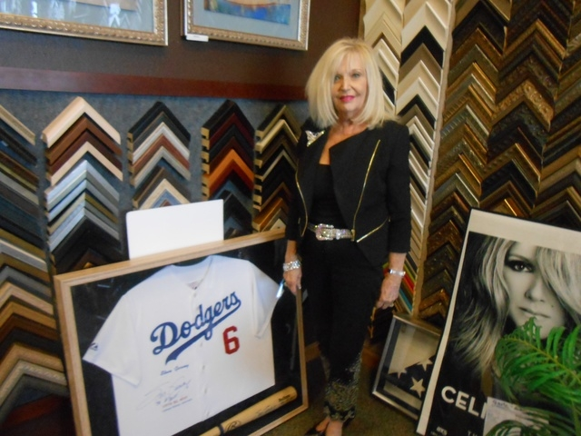 Lynda Rolen shows off a recent project for her framing shop, a Steve Garvey jersey and bat, Feb. 21. She said The Great Frame Up, 10870 W. Charleston Blvd., Suite 110, sees a lot of items that peo ...