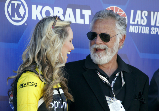 """Johnathan Goldsmith, who portrays """"The Most Interesting Man in the World"""" on TV commercials, speaks with Miss Sprint Cup Kim Coon before the beginning of the Kobalt 400 at the Las Vegas Motor Spee ..."""