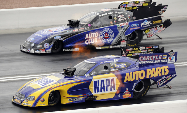 NHRA Funny Car driver Ron Capps, bottom lane, makes a pass of 314.61 MPH at 4.075 seconds elapsed time alongside Funny Car driver Robert Hight in the third qualifying session for the SummitRacing. ...