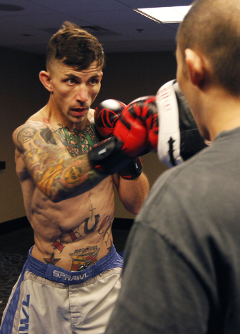Iraq War veteran Shane Kruchten, left, spars with his friends and training partner Victor Chen while preparing for his upcoming World Series of Fighting mixed martial arts bout at the Hard Rock Ho ...