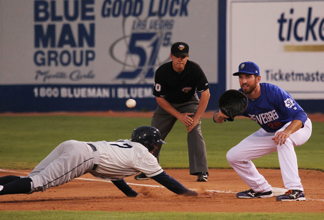 The 51s first baseman Ike Davis tries to pick off the Tacoma Rainiers' Brad Miller at Cashman Field in Las Vegas on June 11, 2013. (Jason Bean/Las Vegas Review-Journal)