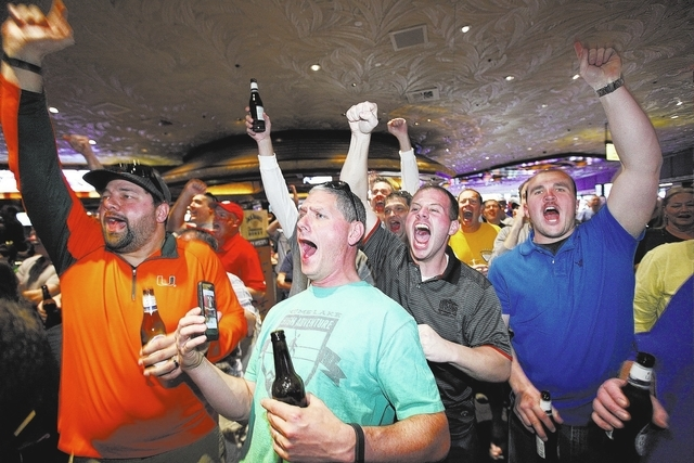 From left, Rodney Faulk, R.T. Browning, Nicholas Larotonda and Cody Malia cheer as they watch Dayton defeat Ohio State in the NCAA basketball tournament on a screen in the sports book at the Mirag ...