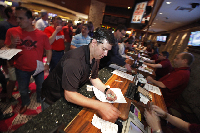 James Grundy places a bet on the NCAA basketball tournament in the sports book at The Mirage in Las Vegas Thursday, March 20, 2014. (John Locher/Las Vegas Review-Journal)