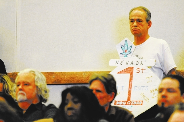 William Baker, member of marijuana patient advocate group WECAN, holds a sign in support on a new ordinance that would allow dispensaries for medical marijuana in Clark County during an open forum ...