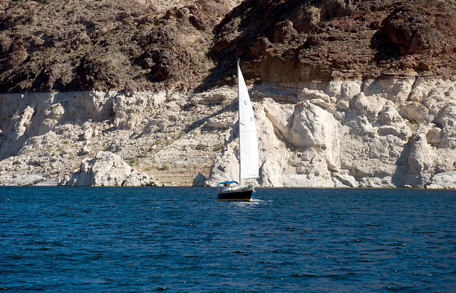 """A sailboat cruises on Lake Mead on Sunday, Oct. 20, 2013. The white """"bathtub ring"""" in the background shows the drop in the lake level in recent years. California will soon start drawing  ..."""