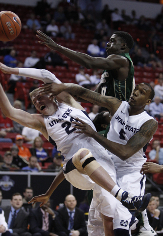 Utah State player Kyle Davis, left, gets fouled by Joe De Ciman, top right, of Colorado State during the first round of the Mountain West Championships tournament at the Thomas & Mack Center in La ...