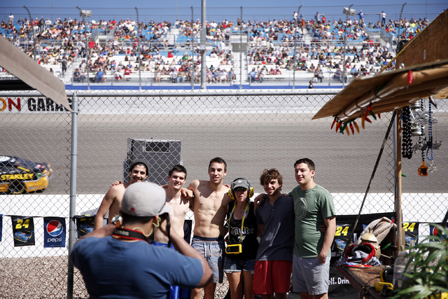 Fans have their picture taken during the NASCAR Kobalt 400 in Las Vegas Sunday. More than 100,000 fans came to Las Vegas for that race. (John Locher/Las Vegas Review-Journal)