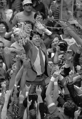 In this April 4, 1983 file photo, North Carolina State coach Jim Valvano holds the net aloft after his team defeated Houston 54-52 for the national championship in the Final Four of the NCAA colle ...
