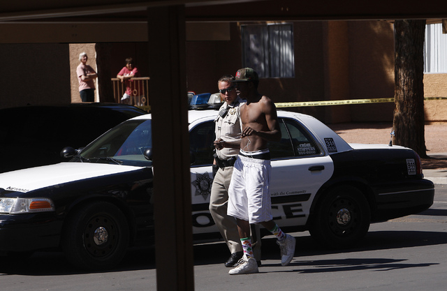A Metro Police officer talks with a potential witness to a shooting at Nellis Gardens apartment complex in Las Vegas on March 19, 2014. (Jason Bean/Las Vegas Review-Journal)