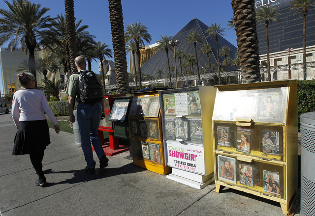 People walk past a row of newsracks in front of the Luxor on the Las Vegas Strip on Tuesday. (Jason Bean/Las Vegas Review-Journal)