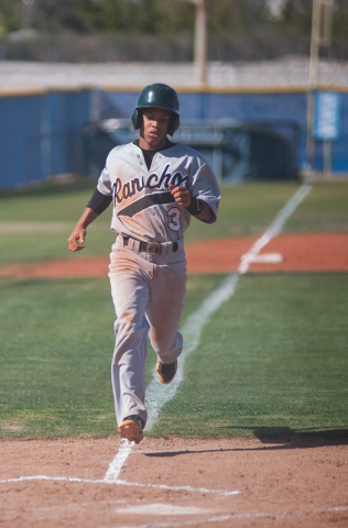 Rancho senior Bryce Harrell scores a run in the top of the first inning on Friday at Centennial. The Bulldogs rallied for eight runs in the third inning en route to an 11-7 win over the Rams. (Mar ...