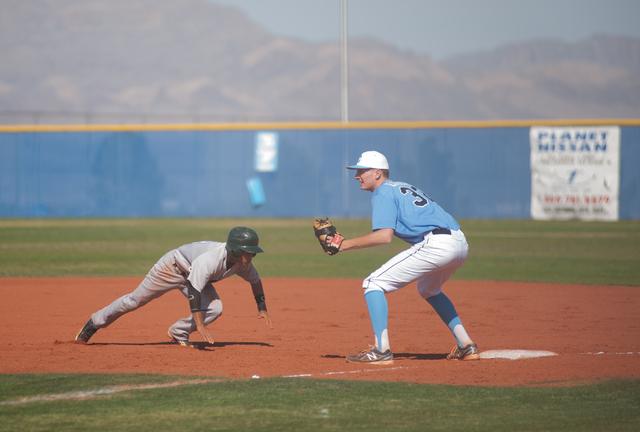 Rancho senior Bryce Harrell dives back to first base as Centennial senior Will Loucks awaits a throw. (Martin S. Fuentes/Las Vegas Review-Journal)