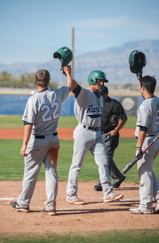 Rancho senior Jose Verdugo, center, is congratulated by teammates from left, Dylan Pletsch and David Modler after he hit a two-run home run in the third inning Friday against Centennial. (Martin S ...