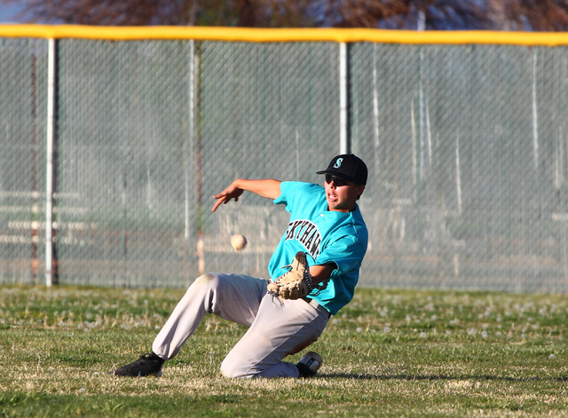 Silverado outfielder Aidan Adams (8) slides to catch a fly ball hit by Palo Verde's Kevin Smith in the seventh inning on Friday. Silverado won the game 11-8. (Chase Stevens/Las Vegas Review-Journal)