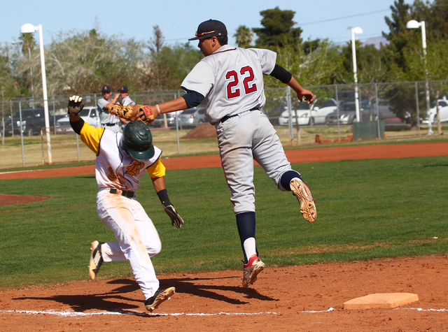 Rancho's Bryce Harrell (3) evades Liberty's Omar Ortiz (22) as he attempts to tag Harrell out at first base during a game at Rancho High School in Las Vegas on Saturday, March 15, 2014. (Chase Ste ...