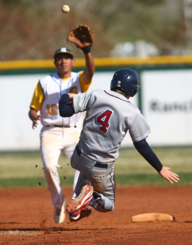 Liberty's Jay Martz (4) jumps to slide safely into second base as Rancho's Juan Cruz (12) reaches to catch the ball during a game at Rancho High School in Las Vegas on Saturday, March 15, 2014. (C ...