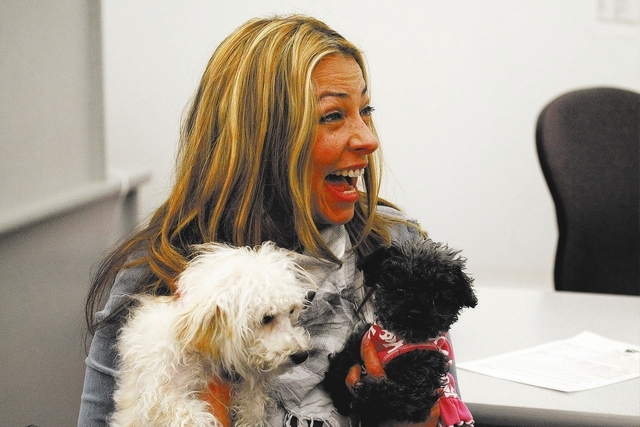 Trina Pascucci holds Aideen,left, a poodle mix that was rescued from the Prince and Princess pet store fire in January, and Maddie, a dof she has owned for years, shortly before adopting Aideen at ...