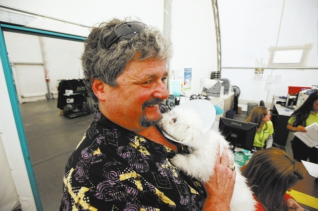 Billy Sottile holds CJ, a maltese puppy that was in the Prince and Princess pet store fire in January, shortly before adopting the animal at the Animal Foundation LIED Animal Shelter in Las Vegas  ...
