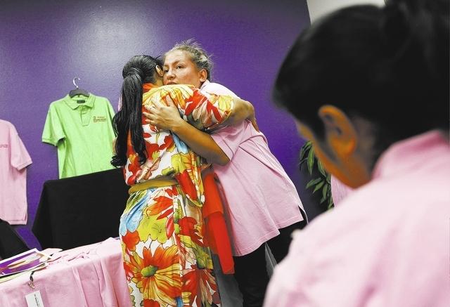 Rebeca Ferreira, left, hugs Belem Ortega during a class on getting a job held at her organization Safe Faith United in Las Vegas Friday, Feb. 21, 2014. Ortega is victim of domestic violence. (John ...