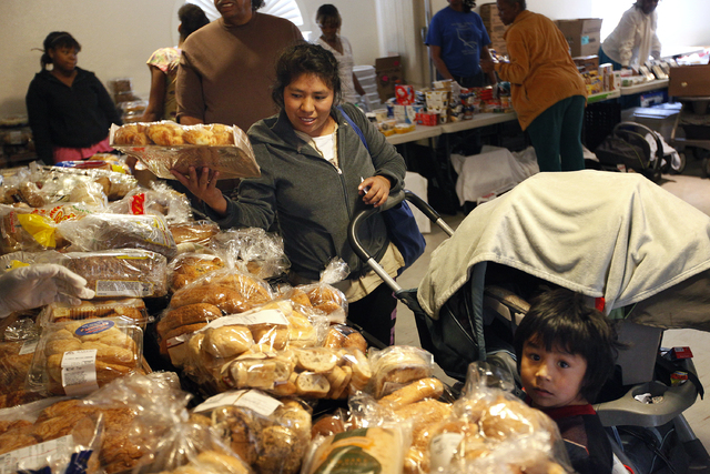 Catarina Cano, left, and her three-year-old son Roberto Cano receive food at the Macedonia Outreach Social Enrichment Services food pantry on North Las Vegas Thursday, Feb. 27, 2014. (John Locher/ ...