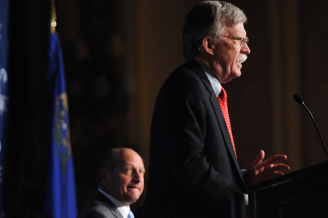 David Flaum, left, chairman at the Republican Jewish Coalition, watches John Bolton, former U.S. Ambassador to the United Nations, speak during the Republican Jewish Coalition's annual conference  ...