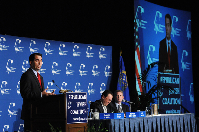 Matt Brooks, from right, executive director at the Republican Jewish Coalition, and Chairman David Flaum, listen to Wisconsin Gov. Scott Walker speak during the Republican Jewish Coalition's annua ...