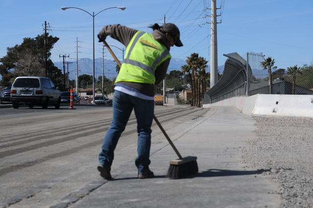 Michelle Wilson, flagger with the Las Vegas Paving Corp., sweeps the sidewalk at the Las Vegas Wash bridge on East Sahara Avenue near the Desert Rose Golf Course in Las Vegas Tuesday, March 11, 20 ...